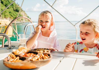two beautiful young ladies enjoying a snack during their sailing and snorkeling trip in nevis